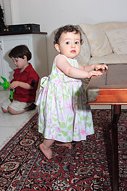 A baby girl stands near a table